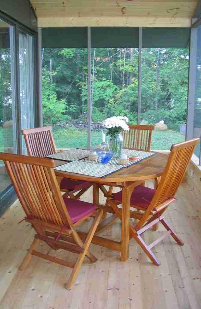 Screened in cottage porch with teak table and chairs
